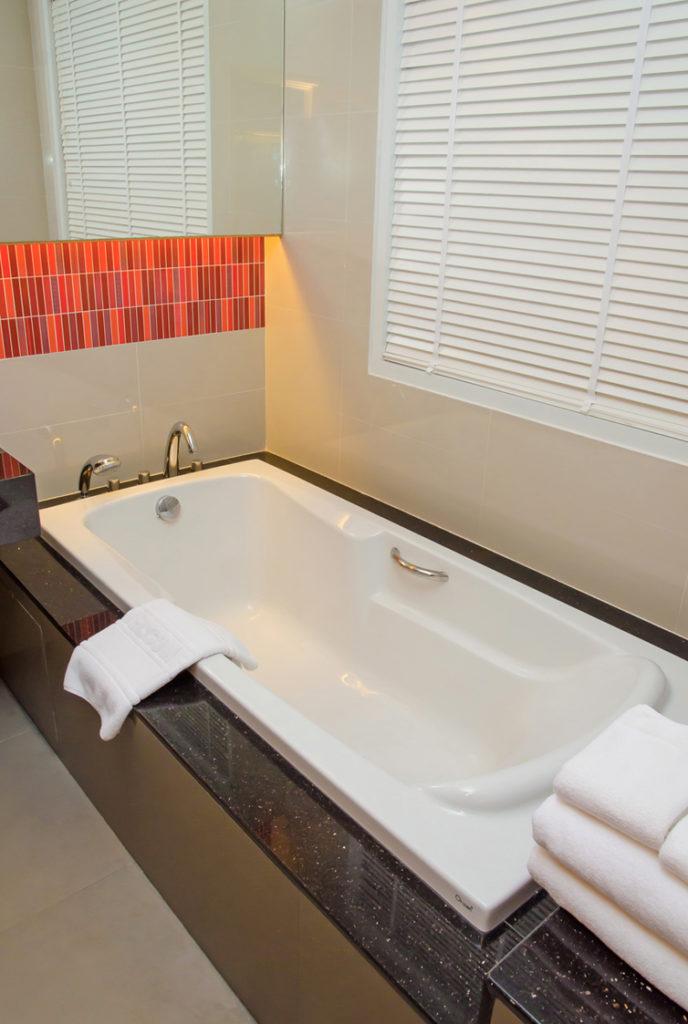 weiße Badewanne mit braune und orange Fliesen