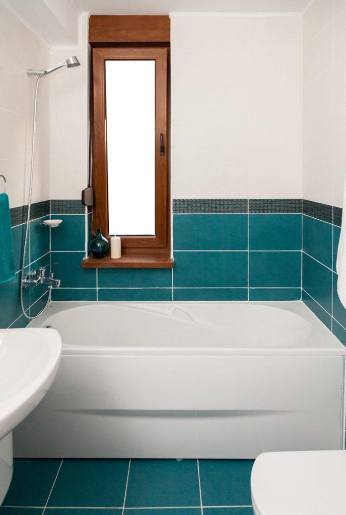 weiße Badewanne mit grünen Fliesen