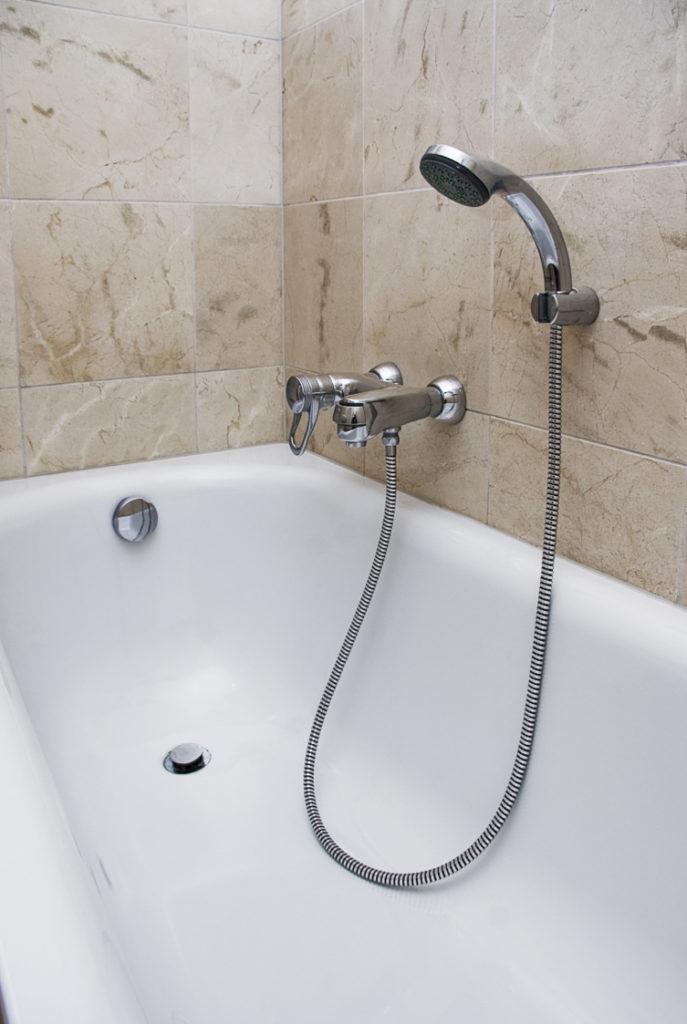 weiße Badewanne mit braunen Fliesen