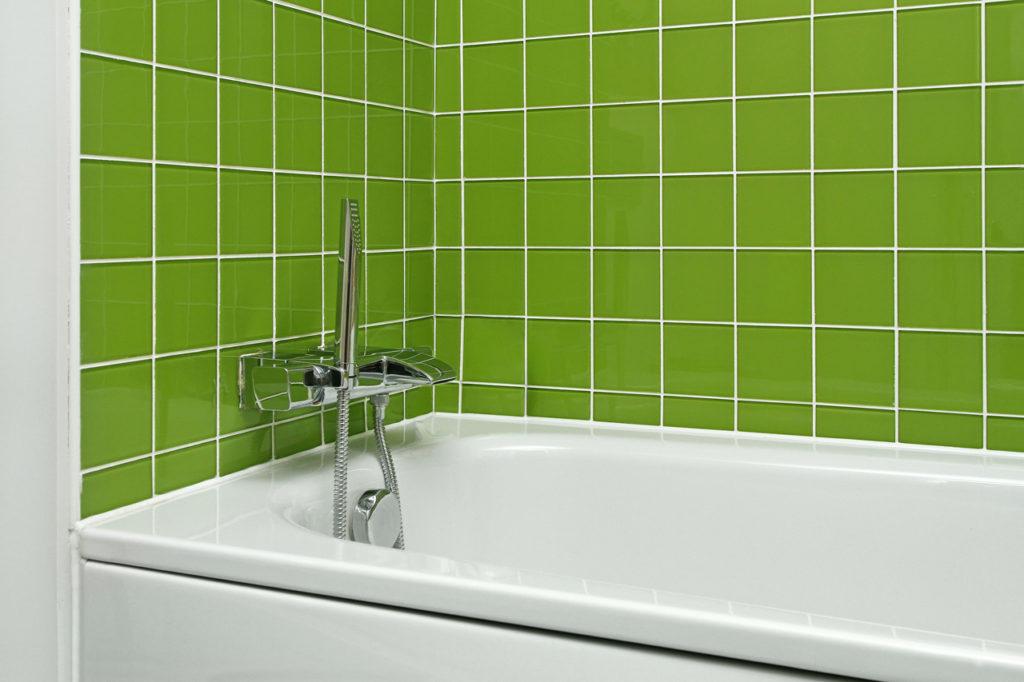 weißes Badewanne mit grünen Fliesen